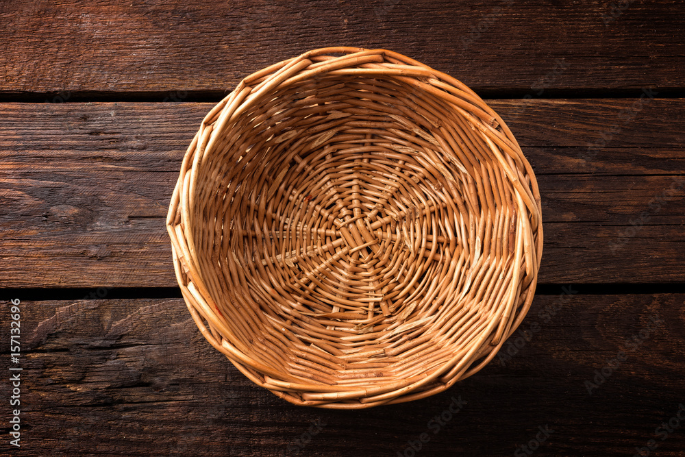 Fototapety, obrazy: Empty wicker basket on a wooden background, top view