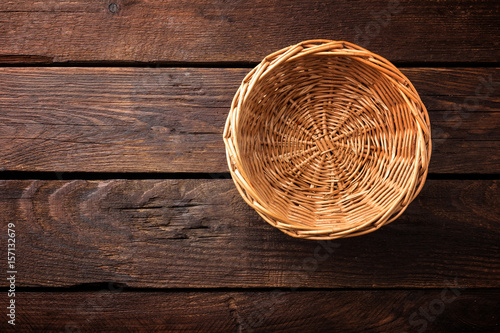 Fotografía  Empty wicker basket on a wooden background, top view