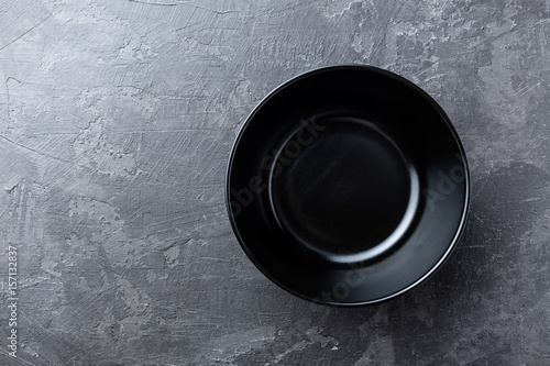 Empty black soup plate on dark grey background, top view