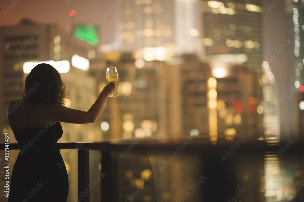 Photo  Beautiful young woman on the balcony in a black dress with a glass of wine on th