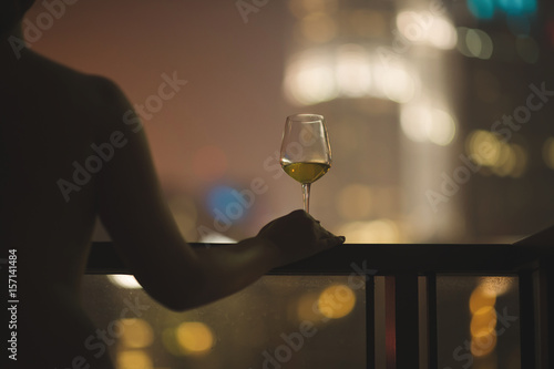 Beautiful naked female on a balcony with a glass of white wine on a background of a night city in Kuala Lumpur Canvas Print