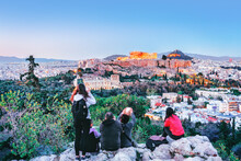 People In Athens Sightseeing At Acropolis Ancient Building From Philosophy Hill, Sunset Scenery. Greece.