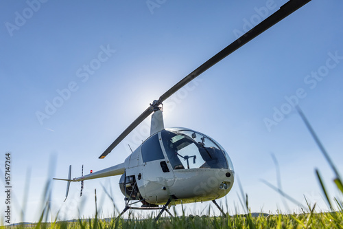 Türaufkleber Hubschrauber Small Robinson R22 light utility helicopter parked on grass airport. One of the world's most popular light helicopters with twin blades and a single engine