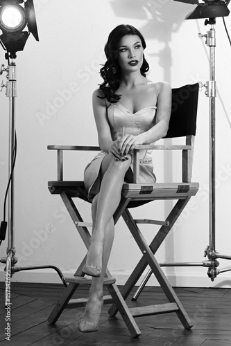 Photo  Young pretty beautiful woman in elegant dress with makeup, red lips and classical hollywood waves hairstyle sitting in director's chair at film set with two cinema lights