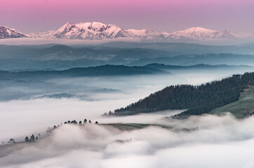 FototapetaBeautiful spring panorama over misty Spisz highland to snowy Tatra mountains in the morning, Poland
