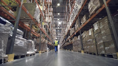Back view. Female warehouse worker walks through rows of storage racks with merchandise