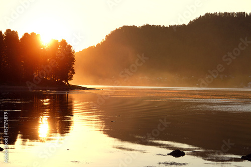 Beautiful summer sunset on the lake. Sun's rays Shine through the trees in the evening on the lake. Camping, coastline