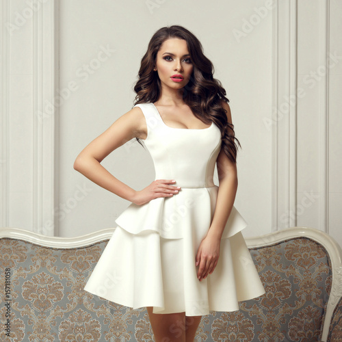 Foto  Young elegant woman in white dress with circular skirt standing in bright interior against sofa and white wall and looking at you