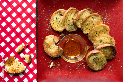 Fotografie, Obraz  french bread slices with olive oil on red plate and checkerboard tablecloth