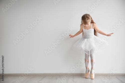 Fototapeta  Beautiful little ballerina in light dance studio