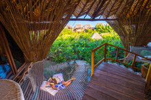 Woman Laying On Net In Treehouse