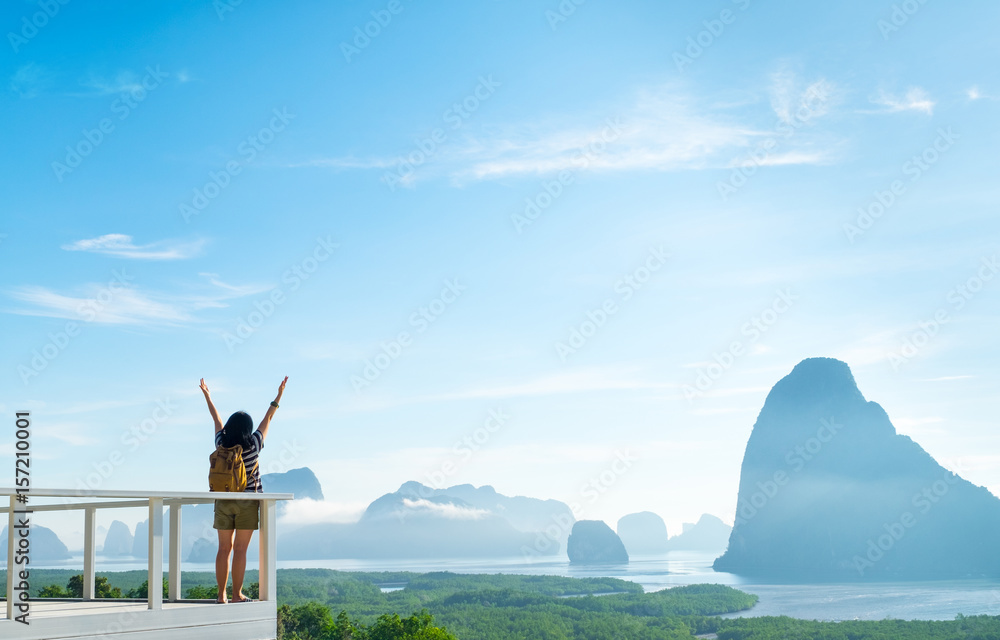 Fototapety, obrazy: Happy young traveler woman backpacker raised arm up to sky enjoying a beautiful of nature at mountain panorama view point and sea,Freedom wanderlust,Khao Samed Nang Chee Viewpoint,Phang Nga,Thailand.