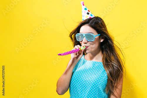 Fotografie, Obraz  Young woman with party hat with noisemaker