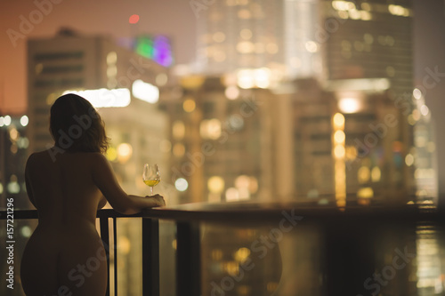Photo  Beautiful naked female on a balcony with a glass of white wine on a background of a night city in Kuala Lumpur