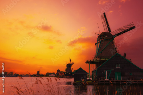 Traditional Dutch windmills on the canal bank at warm sunset light in Netherland Plakat