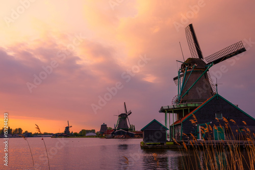 Traditional Dutch windmills on the canal bank at warm sunset in Netherlands near Plakat