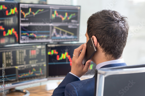 Obraz Over the shoulder view of and stock broker trading online while accepting orders by phone. Multiple computer screens ful of charts and data analyses in background. - fototapety do salonu
