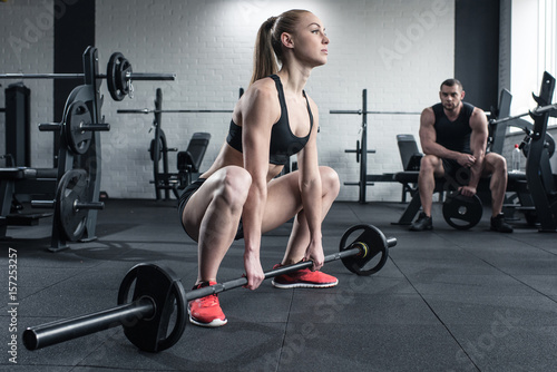 Deurstickers Fitness woman doing strength training with barbell while man sitting at gym