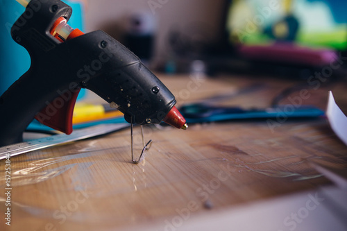 Closeup of glue gun on wooden table Wallpaper Mural