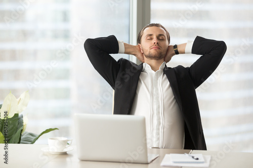 Tired Businessman Sitting At Work Desk With Laptop Resting