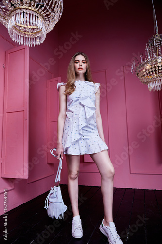 Beautiful sexy pretty woman long blond hair wear casual style clothes for party fashion model pose accessory hand bag interior design room pink wall chandelier shine. Wall mural