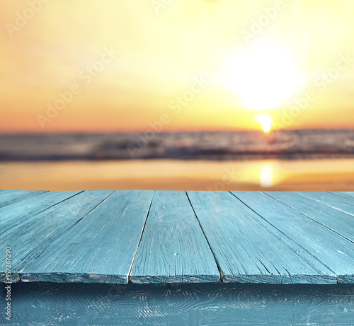 blue table top against blurred sunset beach background - Buy