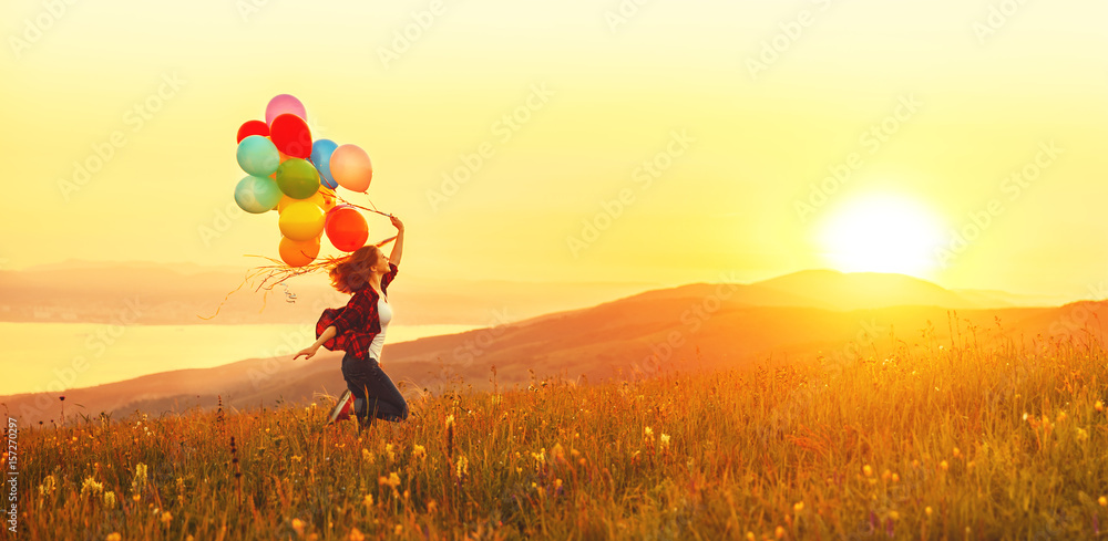 Fototapeta Happy cheerful girl with balloons running across meadow at sunset in summer