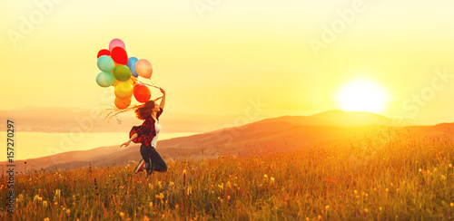 Fotografie, Obraz  Happy cheerful girl with balloons running across meadow at sunset in summer