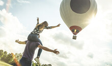 Happy Couple In Love On Honeymoon Vacation Cheering At Hot Air Balloon - Summer Travel Concept With Young People Travelers Having Fun At Trip Excursion - Vintage Contrast Retro Filter With Backlight