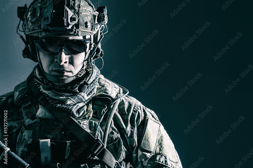 Fototapeta Elite member of US Army rangers in combat helmet and dark glasses. Studio shot, dark black background, looking at camera, dark contrast
