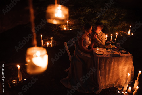 Romantic dinner of a young couple by candlelight in the mountains