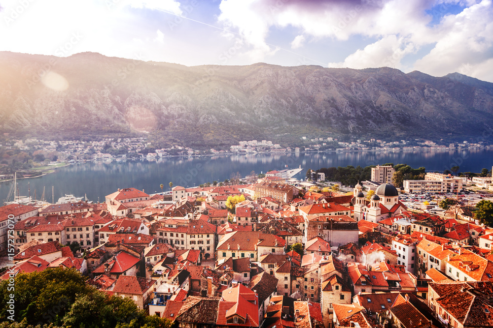 iew of the roofs of the houses and the marina with a fortress wall in the old town of Kotor, Montenegro