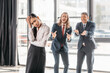frustrated asian businesswoman standing in office, businessmen behind gesturing and laughing