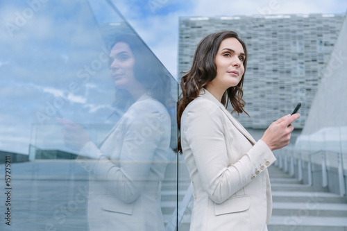 Young woamn leaning on a window using her phone