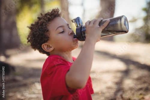 Boy drinking water after workout during obstacle course