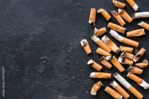 Fényképezés  Cigarette butts on a black background with space for text
