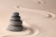 balancing a stack of black hot stones for spa wellness therapy. Zen meditation rock andsand garden. A yoga background.