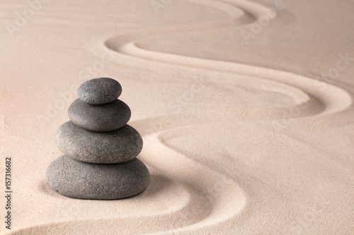 Acrylic Prints Stones in Sand balancing a stack of black hot stones for spa wellness therapy. Zen meditation rock andsand garden. A yoga background.