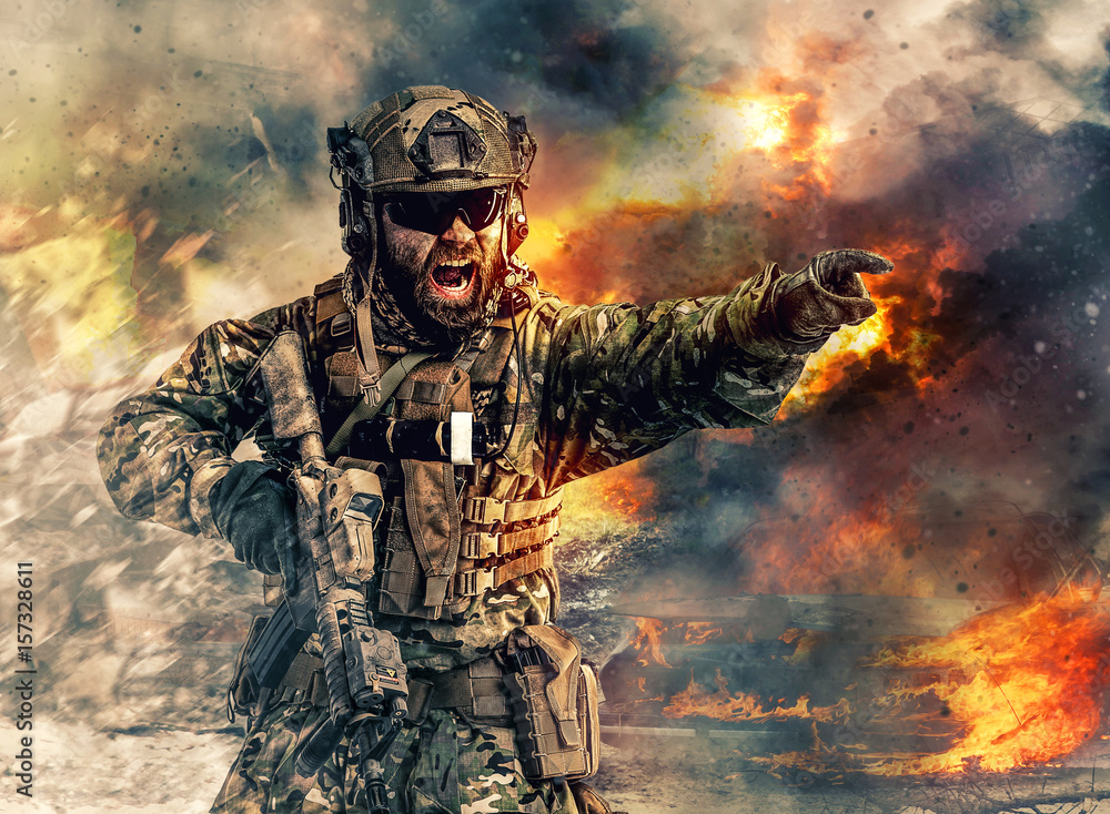 Fototapeta Bearded soldier of special forces in action pointing target and giving attack direction. Burnt ruins, Heavy explosions, gunfire and smoke billowing on background
