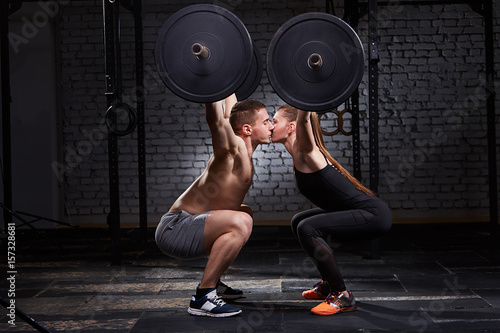Poster Fitness Young beautiful sportive woman and man kissing and lifting a dumbbell from squats against brick wall in the gym.
