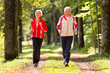 Senior Couple doing sport outdoors, jogging on a forest road in the autumn