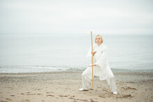European Caucasian Adult Woman In White Clothes Practicing Chinese Traditional Art Taijiquan In Beautiful Nature. Exercise With Staff In Morning Day On The Sea Coast. Selective Focus