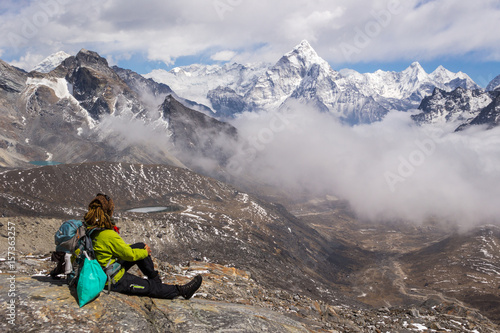 Young Woman hiker with backpack and hiking poles is sitting and looking on Ama Dablam mountain Poster