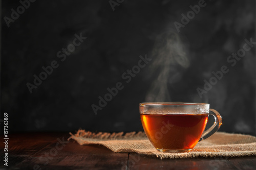 La pose en embrasure The A Cup of freshly brewed black tea,escaping steam,warm soft light, darker background.