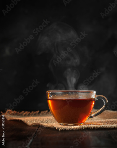 Staande foto Thee A Cup of freshly brewed black tea,escaping steam,warm soft light, darker background.