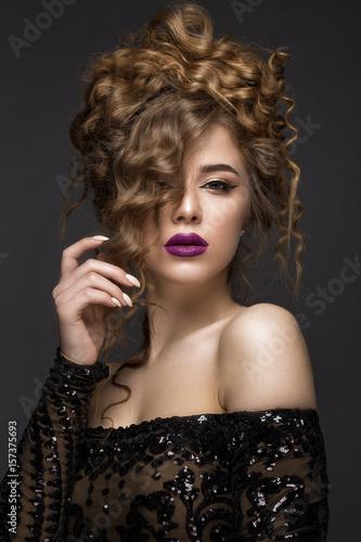Zdjęcie XXL Piękna brunetka o idealnie kręconych włosach i klasycznym makijażu. Piękna twarz. Obrazek brać w studiu na szarym tle.