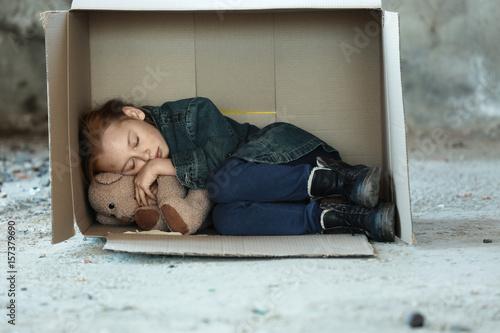 Poor little girl sleeping in cardboard box on street Canvas Print