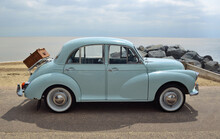 Classic Light Blue Morris Minor With Picnic Basket Parked On Seafront Promenade.