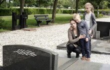 Young Widow Visiting Graveyard With Kids