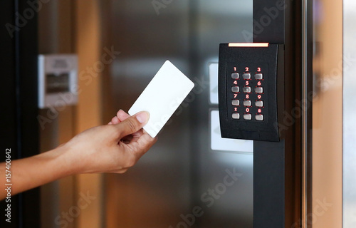 Fotografía Door access control - young woman holding a key card to lock and unlock door